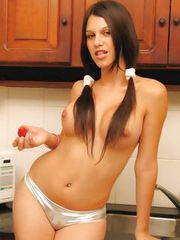 Luscious brunette shemale showing her massive breasts in the kitchen